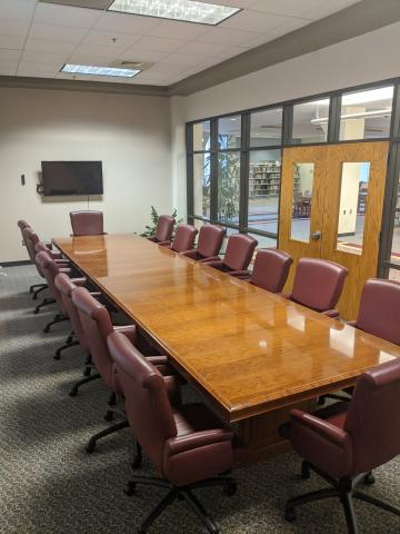 Room photo of the Wren Meeting Room showing long conference table with chairs all around it and a mounted television